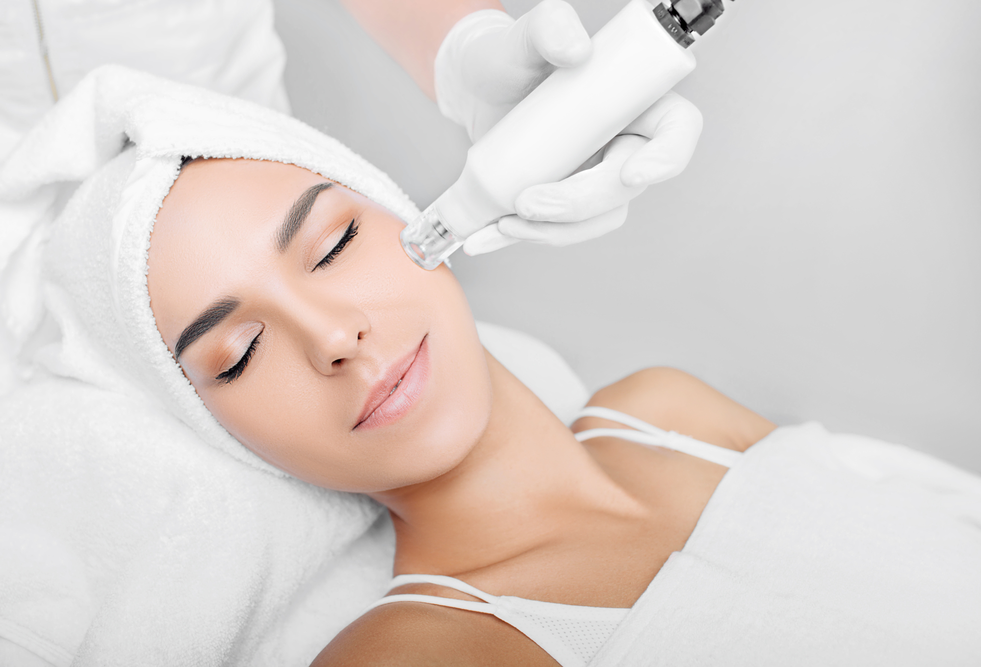 relaxed woman receiving microneedling treatment to her face