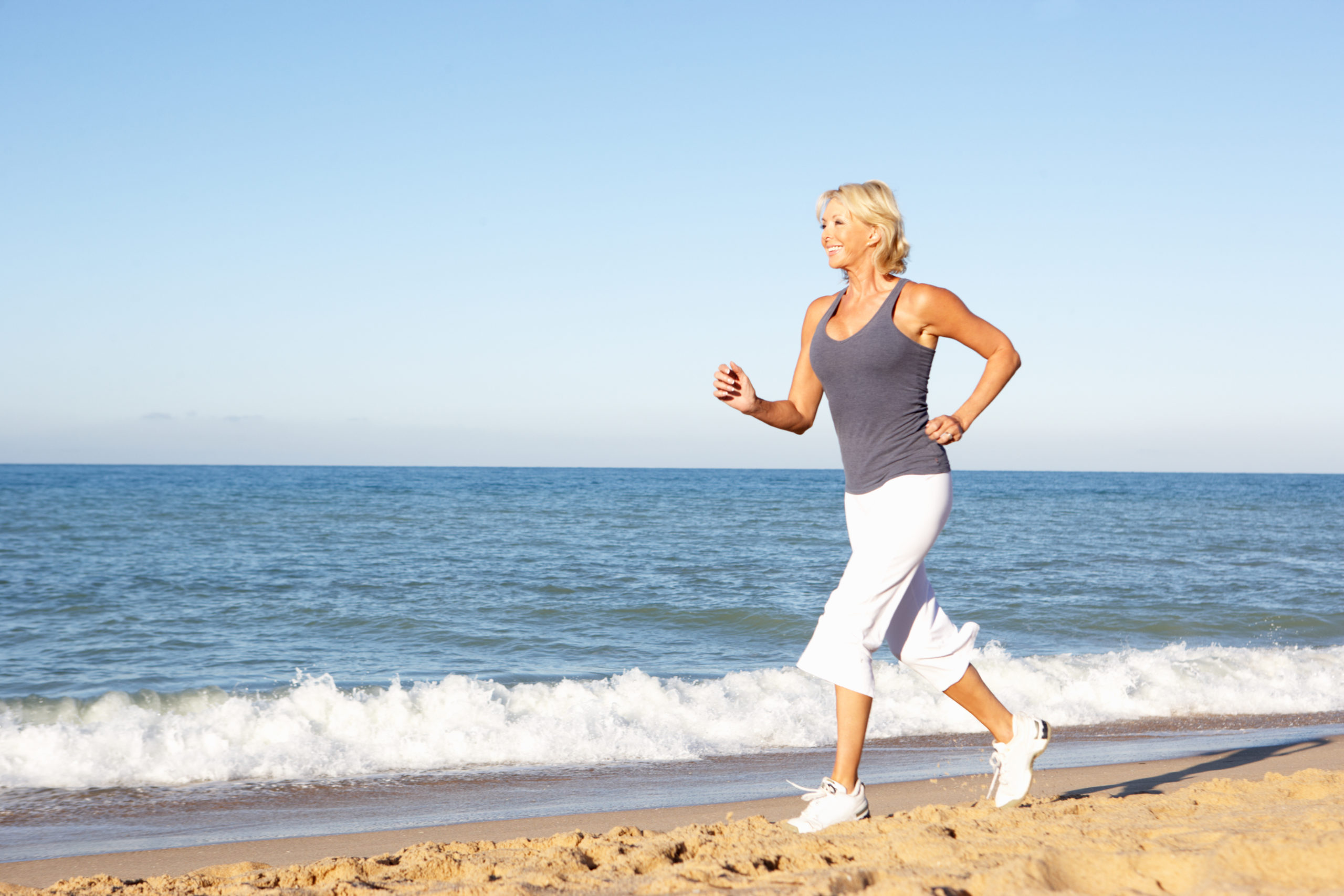 woman jogging along beach after IV Therapy