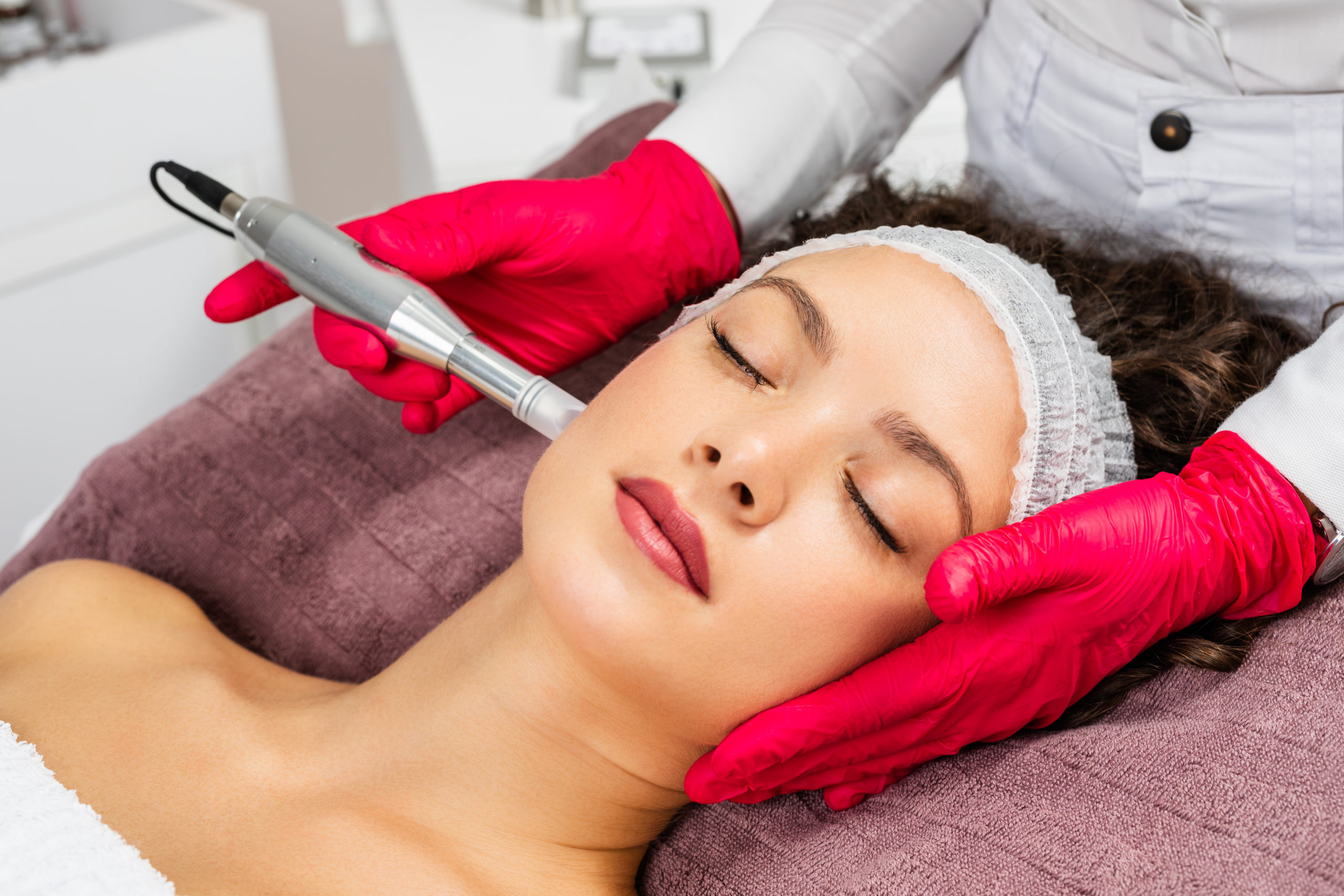 aesthetician applying microneedling treatment to woman's face