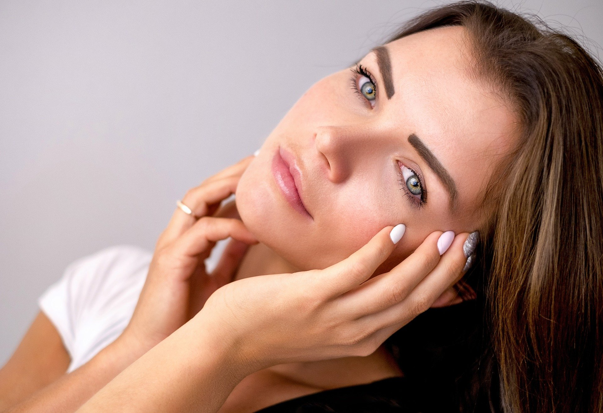 youthful woman touching her face after microneedling
