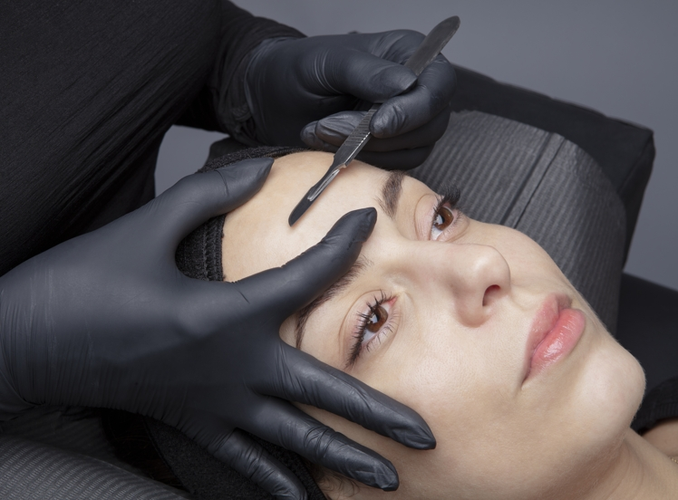 aesthetician demaplaning a woman's forehead