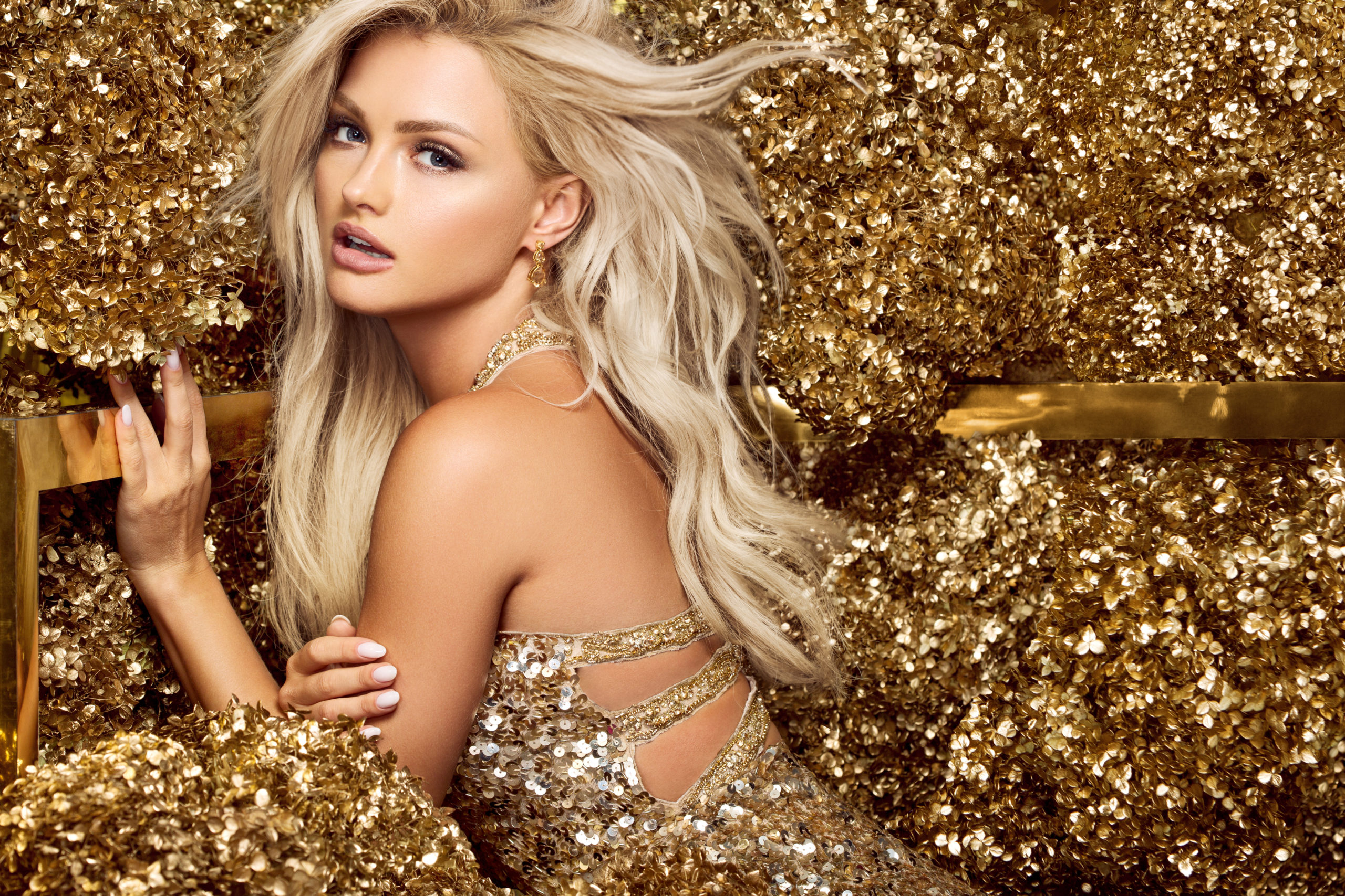 beautiful blonde woman showing AQUAGOLD® flawless skin surrounded by gold glitter and sequins